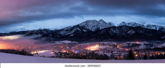 Giewont and Tatra Mountains after sunset. Winter evening and a fog after heavy rain. Zakopane at evening time and city lights.