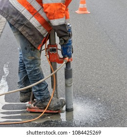 Gifhorn, Lower Saxony, Germany - April 26, 2018: Workers with reflective warning vest drill a core hole in the asphalt of a through road closed off for the duration of the work.