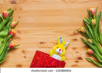 Gift bag with a bunny and a bouquet of flowers on a wooden table, blank, background