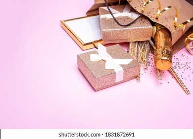 Gift bag with christmas presents, with champagne on pink background