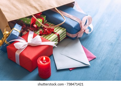 Gift bag overturned on the table - Shopping bag full of colorful presents, paper wrapped and tied with ribbon and bows, overturned on a blue wooden table, over closed envelopes, near a red candle.