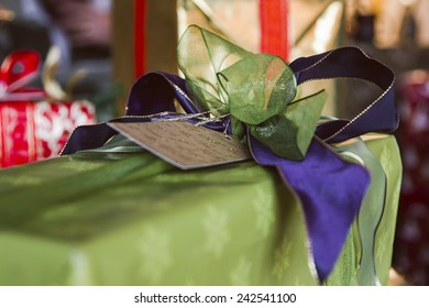 A gift, beautifully wrapped in green and purple, at Christmas.