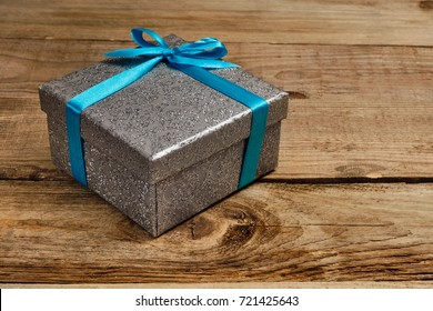 Gift birthday Christmas present concept - silver gift box with blue ribbon on old wooden background