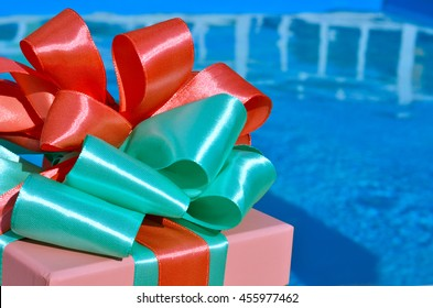 Gift box against the background of the blue pool.