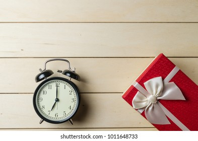 gift box and alarm clock on wooden board background
