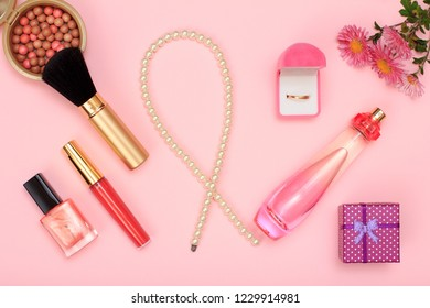 Gift box, beads, bottle of perfume, nail polish and golden ring in box, powder on a pink background. Women cosmetics and accessories. Top view.