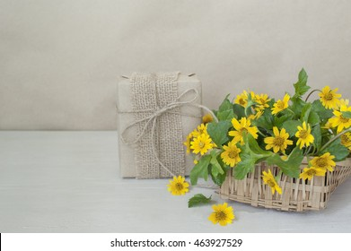 Gift box beautiful bouquet of bright yellow flowers in basket on wooden table,vintage tone.