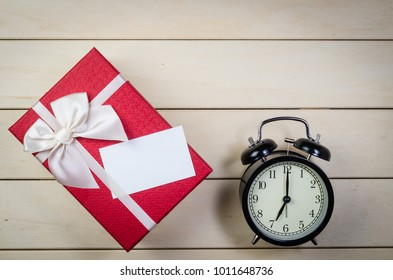 gift box with blank name card and alarm clock on wooden board background