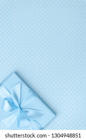 Gift box with blue ribbon bow on blue speckled background top view. Holiday concept, birthday gift, 8 march or Women day, gift box presents holiday Mothers day. Greeting card with space. Flat Lay.