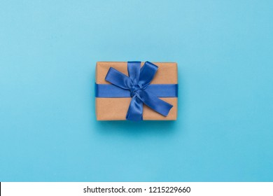 Gift box with blue ribbon on a blue background. Holiday, birthda