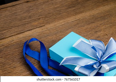 gift box with blue satin bow on wooden board background,