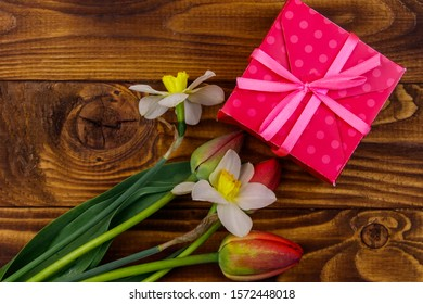 Gift box and bouquet of red tulips and daffodils on wooden background. Concept of Valentine's Day, Women's Day, Mother's Day and Birthday. Top view, copy space
