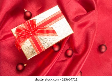 Gift box with bow, on red wavy satin fabric with Christmas balls.