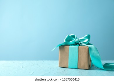 Gift box with bow on turquoise background, space for text