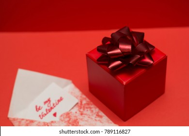 gift box with bow  and white lable with inscription be my valentine  on a red background