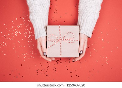 Gift box with bow in woman's hands. Living Coral - Color of the Year 2019.