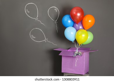 Gift box with bright air balloons and chalk drawing on grey background