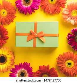 Gift box with bright beautiful gerbera flower on sunny yellow background. The concept of the New Year, Christmas, Birthday, Anniversary. Top view. Flatlay