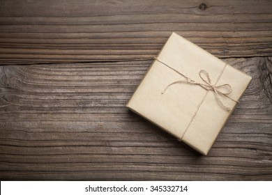 Gift box with brown paper on wood background
