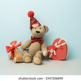 gift box and brown teddy bear in a red cap sits on a blue background, festive background
