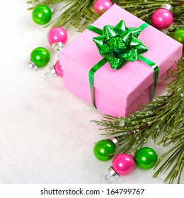 Gift box with Christmas baubles and pine branches on snow background