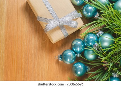 Gift box for Christmas party, hand made with brown paper tight with silver ribbin put on floor with background blur of blue christmas ball and green leaf of pine tree. Happy season with family.