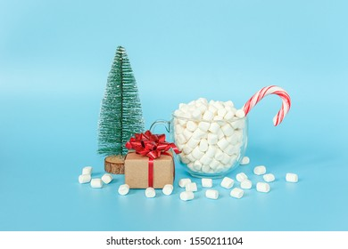 Gift box, christmas tree and cup of marshmallows with red lollipop cane on blue background. Merry Christmas or Happy New Year concept. Template for your design, Greeting card.