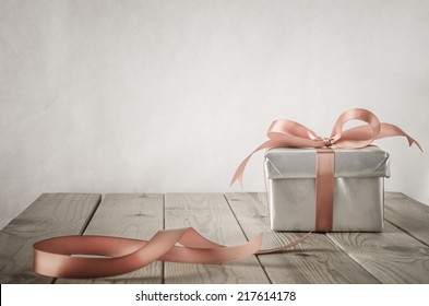 A gift box with closed lid, wrapped in silver paper and tied to a bow with a satin ribbon.  Placed on a weathered old wooden table with copy space behind and above. Cut ribbon remnant to the side.