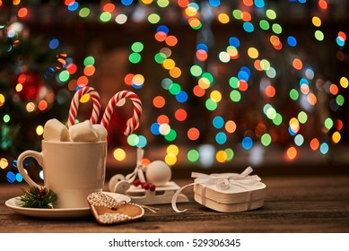 Gift box and a cup of coffee on the table. Xmas lights  background. Holiday concept.