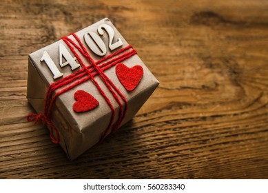gift box with date of happy Valentine's Day. 14 february. two red hearts. present box lie on wooden table background. empty copy space for inscription or objects. holiday backdrop. 14.02