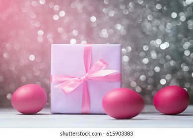 Gift box and Easter eggs over abstract defocused lights