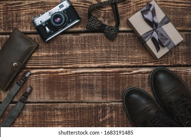 Gift box for father's day with men's accessories bow tie, wallet, retro camera, suspenders and leather shoes on a wooden background. Copy space. Flat lay.