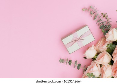 gift box and flowers on pink table from above, flat lay frame