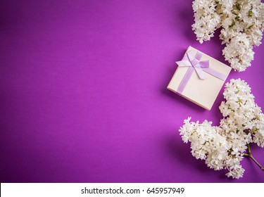 Gift box with flowers on purple background
