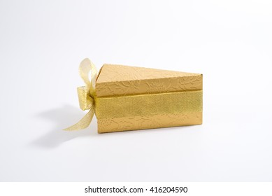 Gift box in the form of a cake with a ribbon. Color is gold.