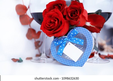 Gift box in the form of a heart of blue. On the background of roses and two glasses with wine.