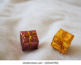 Gift box with gold ribbon and bow on white background