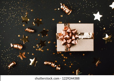 Gift box with golden bow on black background with decoration and sparkles. Flat lay. Festive concept.