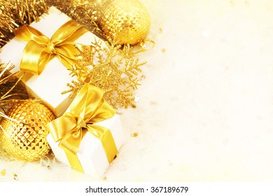Gift box with golden ribbon and light christmas background. Card or invitation.