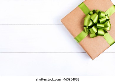 Gift box with green ribbon bow on white wooden background