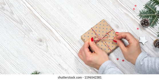 Gift box in hands with Christmas background