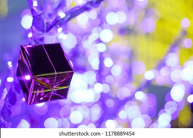 A gift box hang on the Christmas tree with bokeh background in the Christmas and new year event