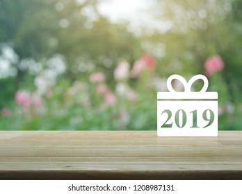 Gift box happy new year 2019 icon on wooden table over blur pink flower and tree, Business shop online concept