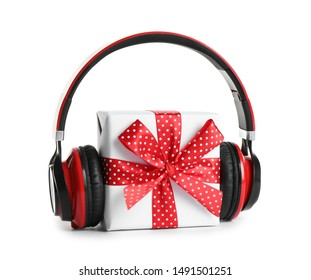 Gift box with headphones isolated on white. Christmas music concept