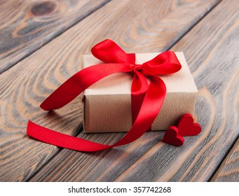 Gift box and hearts on a old wooden background