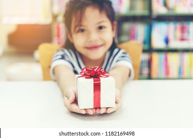 Gift box for kids girl.   White box with red bow in the girl hands for give a gift in the library