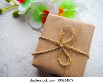 gift box in Kraft paper, wrapped with twine on a white background with the plaster, next to the flower, space for text.
