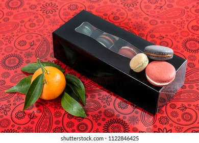 Gift box of macarons on a red swirly table next to a riped tangerine with green leaves
