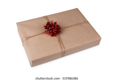 Gift box or mail parcel, post delivery wrapped with kraft paper and twine rope and decorated with red bow isolated on white background. Craft present for christmas, valentine or other holiday