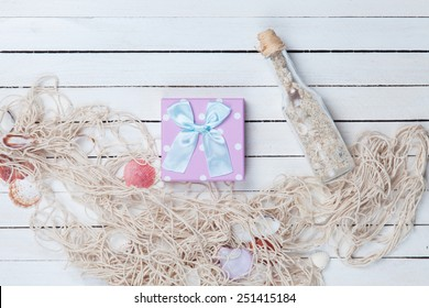 Gift box with net and bottle on white wooden background